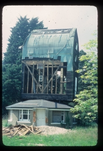 The left side of the mill body is stripped of weatherboards to reveal the framing underneath. The roof of the mill is protected with a tarpaulin